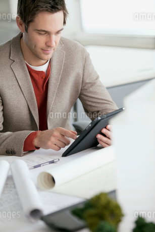 young male architect with blueprintsの写真素材 [FYI02288782]