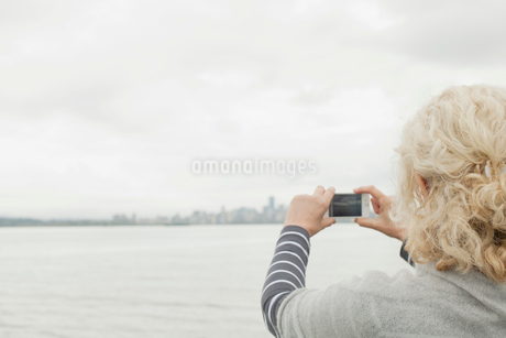 View from behind of senior woman taking picture with cell phone.の写真素材 [FYI02288861]