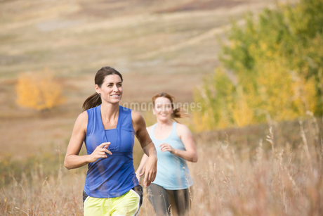 Two women running outdoors together.の写真素材 [FYI02288866]