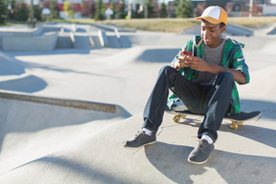 teenager sitting in skate-park texting on smart phoneの写真素材 [FYI02288962]