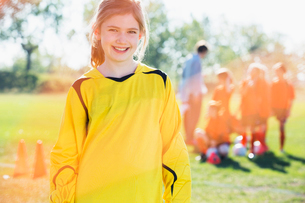 Portrait of young female soccer player with team in background.の写真素材 [FYI02289011]