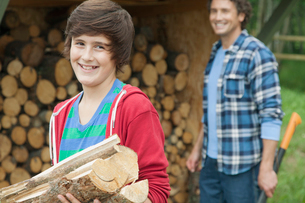 youth getting logs from the wood pile with his dadの写真素材 [FYI02289036]