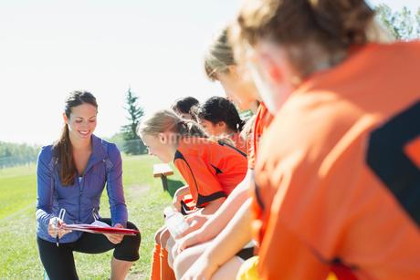 Girls soccer team listening to coach.の写真素材 [FYI02289045]