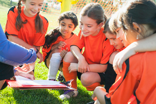 Girls soccer team looking at playbook with coach.の写真素材 [FYI02289081]