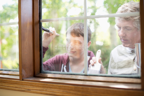 father and son painting exterior window trimの写真素材 [FYI02289258]