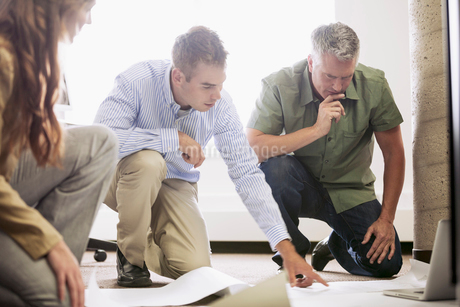 coworkers reviewing blueprints on floor of officeの写真素材 [FYI02289271]