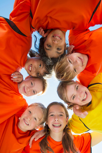 View from below of girls soccer team huddling.の写真素材 [FYI02289273]