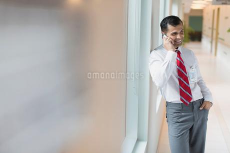 doctor having phone conversation in hallwayの写真素材 [FYI02289275]