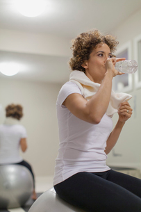 Woman drinking a bottle of water during workout.の写真素材 [FYI02289329]