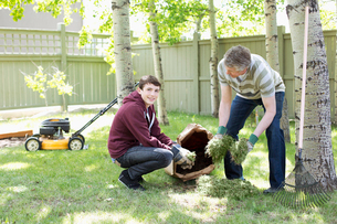 father and son doing yardwork togetherの写真素材 [FYI02289356]