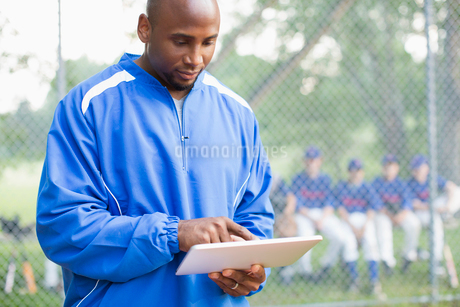 Baseball coach using pc tablet at ball game.の写真素材 [FYI02289378]