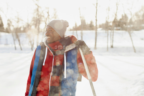 Man standing outdoors in winter with hockey stickの写真素材 [FYI02289442]