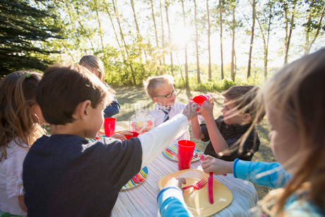 Kids handing out plastic glasses at the kids picnic table.の写真素材 [FYI02289456]