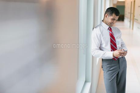doctor texting on smart phone in hallwayの写真素材 [FYI02289457]