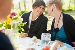 Mother and daughter looking at each other at family dinner.の写真素材 [FYI02289466]