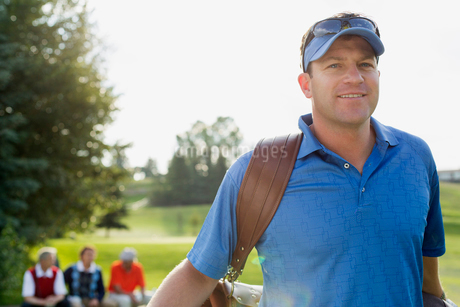 middle-aged golfer walking off tee-box with golf bagの写真素材 [FYI02289497]