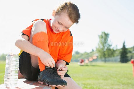 Young female soccer player tying up laces.の写真素材 [FYI02289503]