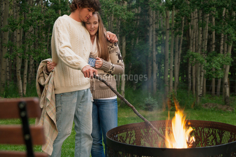 young adult couple cuddling by fire outdoorsの写真素材 [FYI02289552]