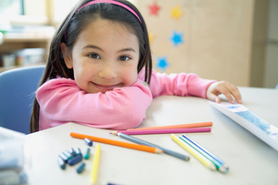 Portrait of cute, elementary student with pencil crayons.の写真素材 [FYI02289556]