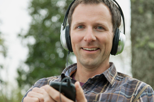 Portrait of mid-adult man with headphones in the parkの写真素材 [FYI02289566]
