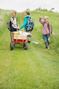 elementary students pulling wagon with field trip suppliesの写真素材 [FYI02289572]