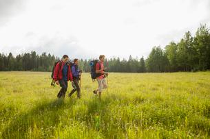 three backpackers walking through meadowの写真素材 [FYI02289578]