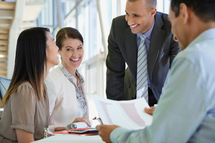 Happy business people talking at desk in officeの写真素材 [FYI02289611]