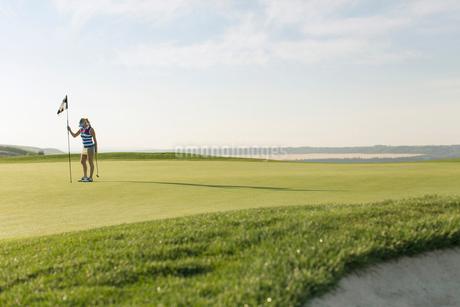 mid-adult female golfer setting flagstick in holeの写真素材 [FYI02289613]