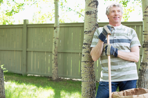 middle aged man doing clean up in yardの写真素材 [FYI02289619]