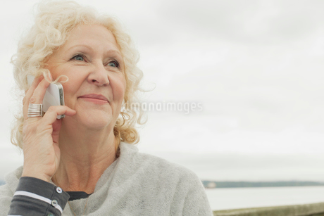 Senior woman on cell phone by waterfront.の写真素材 [FYI02289625]