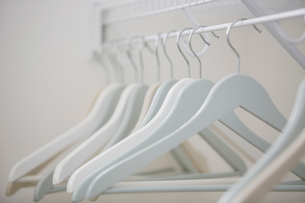 Close-up of white clothes hangers in closet.の写真素材 [FYI02289635]