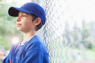 young male baseball player watching game from sidelinesの写真素材 [FYI02289652]