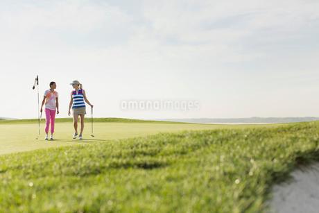 two female golfers walking off golf green togetherの写真素材 [FYI02289665]