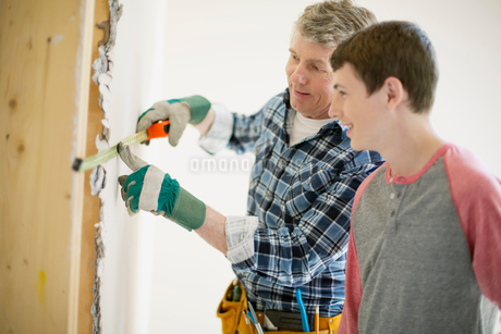 father and teenage son doing home renovationsの写真素材 [FYI02289675]