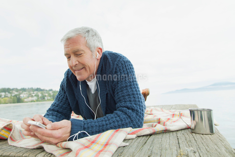 Middle-aged man listening to music on dock.の写真素材 [FYI02289755]
