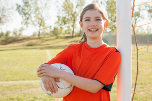 Smiling nine year old female soccer player with soccerball.の写真素材 [FYI02289761]