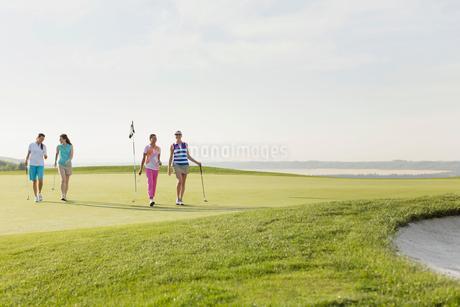 foursome of female golfers walking off greenの写真素材 [FYI02289774]