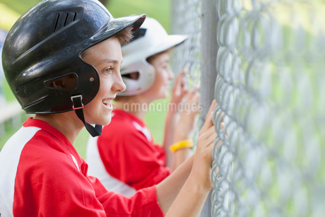 Two young male baseball players watching game from fence.の写真素材 [FYI02289809]