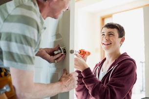 father and teenage son replacing door lockの写真素材 [FYI02289868]