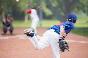 View from behind of young male pitcher throwing baseball.の写真素材 [FYI02289893]