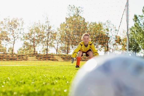 young female goalkeeper defending soccer netの写真素材 [FYI02289903]