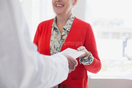 doctor handing prescription to senior womanの写真素材 [FYI02289929]