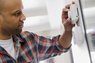 homeowner adjusting new thermostatの写真素材 [FYI02290131]