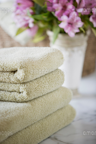 Folded towels on bathroom counter with flowers.の写真素材 [FYI02290146]
