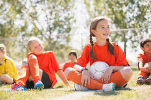 Girls soccer team sitting on grass together.の写真素材 [FYI02290188]