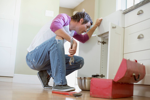 mid adult homeowner repairing plumbing under the sinkの写真素材 [FYI02290189]