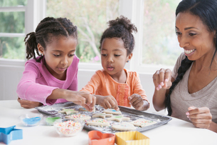 mother and young daughters decorating cookiesの写真素材 [FYI02290274]