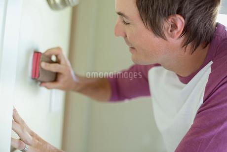 mid adult man sanding wall in kitchenの写真素材 [FYI02290318]