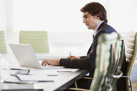 Side view of young businessman using laptop in officeの写真素材 [FYI02290333]