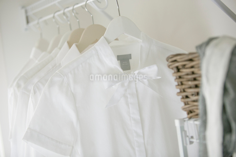 Close-up of white blouse and shirts hanging in closet.の写真素材 [FYI02290403]